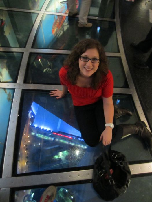 Nicole sitting on the glass floor in the CN Tower in Toronto