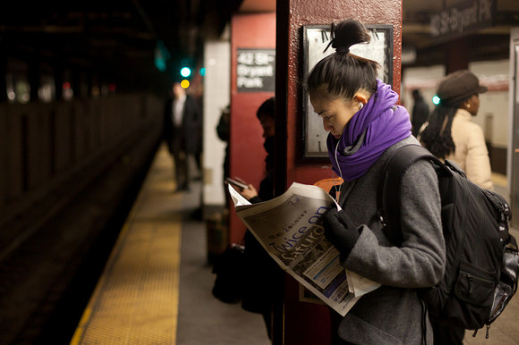 Person reading newspaper on commute